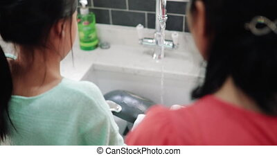 Little girl Learning how to Wash Dishes - Senior woman is...