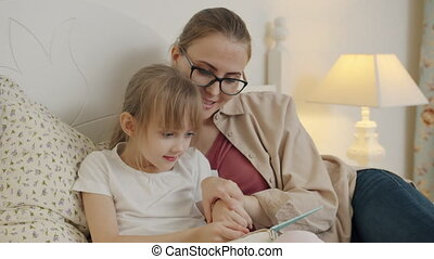 Little girl learning to read reading book with mother in bed...