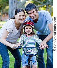 Little girl learning to ride a bike with her parents