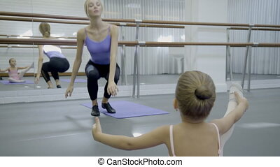 Little girl learns ballet art with teacher in ballet school...