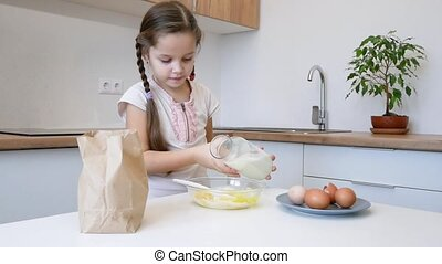 little girl learns to cook in the kitchen and make bakery