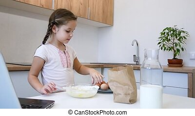 little girl learns to cook in the kitchen and make bakery...