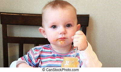 Little girl learns to eat with a spoon independently