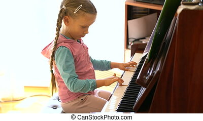 little girl learns to play the piano