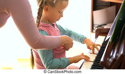little girl learns to play the piano - a five-year-old girl...
