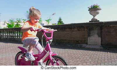 Little girl learns to ride on a bicycle