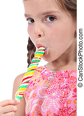 little girl licking a lollipop