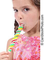 little girl licking a lollipop