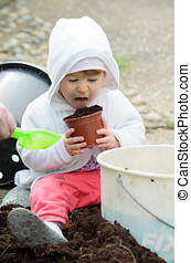 Little girl licking dirt in pot