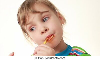 little girl licking lollipop in chicken form - little girl...