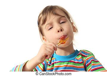 little girl licking orange lollipop, closed eyes, isolated on white
