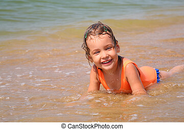 Little girl lies in waves on shore