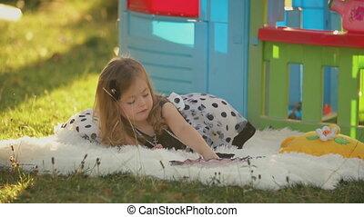 little girl lies on a blanket