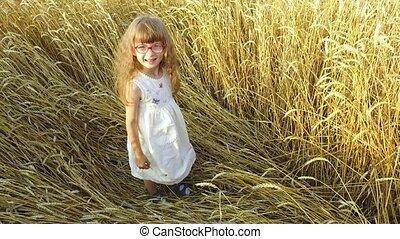 Little girl lies on a haystack Straw in a wheat field. Wheat turned yellow. Soon it will begin harvesting.