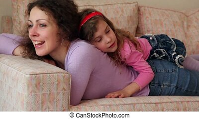 Little girl lies on back of her mother which moves head and sing, closeup view at sofa