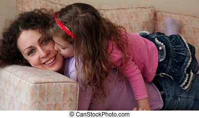 Little girl lies on mother legs and kisses her cheek, closeup view at sofa