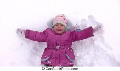 little girl lies on snow