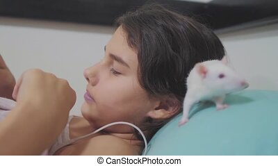 little girl lifestyle is played on a bed with a white homemade handmade rat mouse. funny video rat crawling over a little girl. girl and white mouse lab rat pet concept