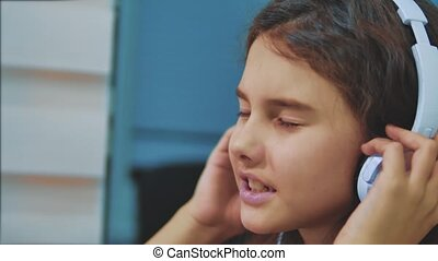 little girl listening to music on headphones on lifestyle...