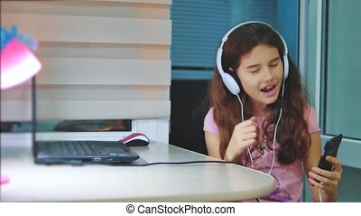 little girl listening to music on headphones on smartphone....