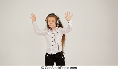 Little Girl Listening to Music With Headphones And Jumping. Locked Down.