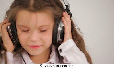 Little girl listens to music