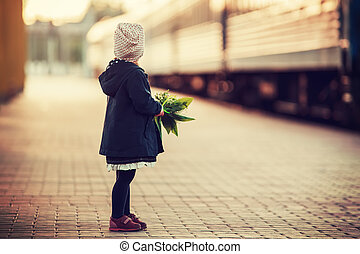 Little girl look at arriving train