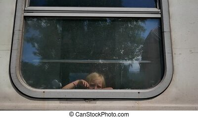 little girl looking and waving from the train window