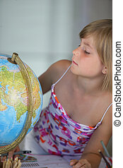 little girl looking at a globe