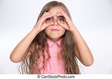 Little girl looking at camera through fingers