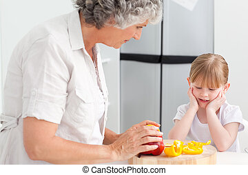 Little girl looking at her grandmother who is cooking