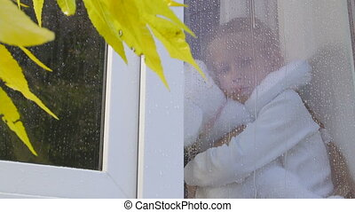 Little girl looking at raindrops on the window glass in autumn