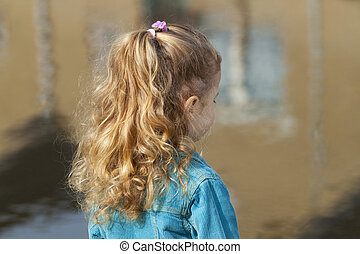 Little girl looking at river.