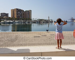 Little girl looking at the Port of Malaga in Andalusia, Spain.