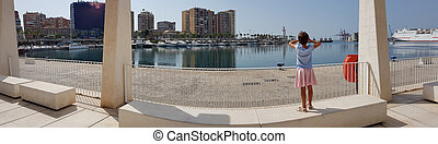 Panoramic view of little girl looking at the Port of Malaga in Andalusia, Spain.