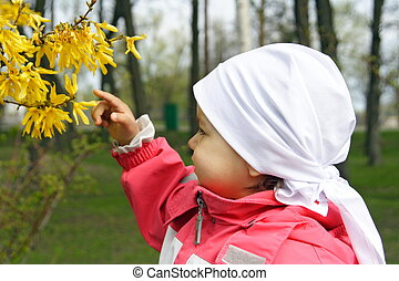 Little Girl Looking at Yellow Flowers
