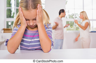 Little girl looking depressed in front of fighting parents...