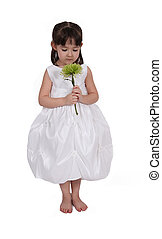 little girl looking down at flower