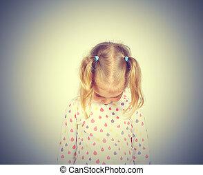 Little girl looking down hurt