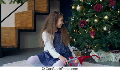 Little girl looking for gifts under Christmas tree - Joyful...