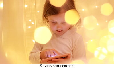 Little girl looking on the smartphone screen and playing in...