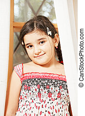 Little girl looking out of curtains
