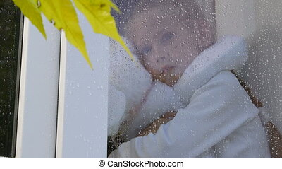 Little girl looking out window on rainy day in autumn