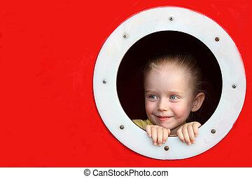 Little girl looking through circle window