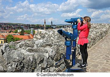 little girl looking through sightseeing binoculars on Eger