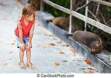 Little girl looking to sea lions