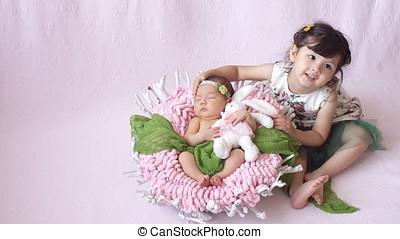 little girl looks at her baby sister