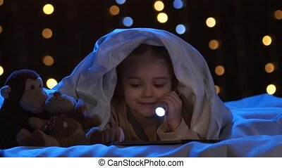 Little girl looks at pictures in a book, she holds a flashlight in her hand. Bokeh background
