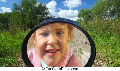 little girl looks in camera through a magnifier