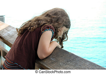 Little Girl Looks Over The Side of a Pier